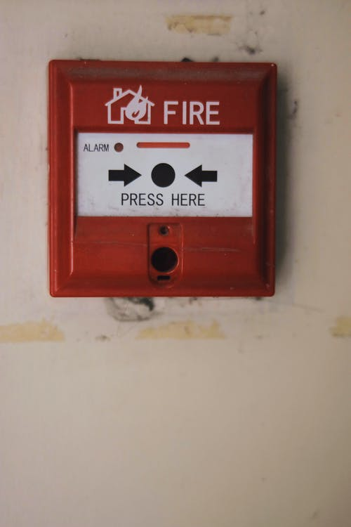 Manual emergency red fire alarm system box with push button placed on white shabby wall in light room of building