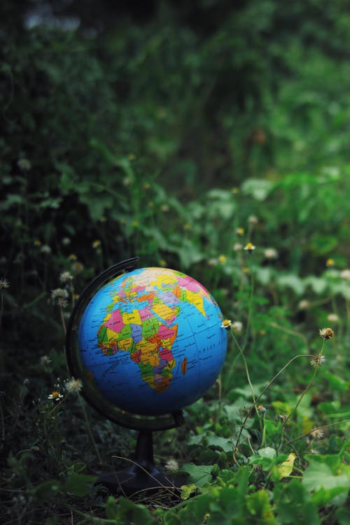 Small Earth globe toy placed on green grass in nature against blurred background in daytime