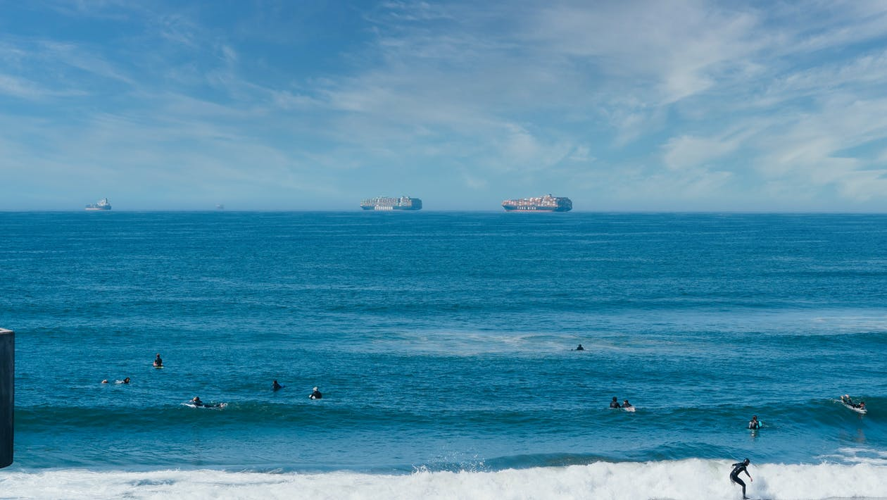 Surfers in the Ocean and Containers Ships on the Horizon
