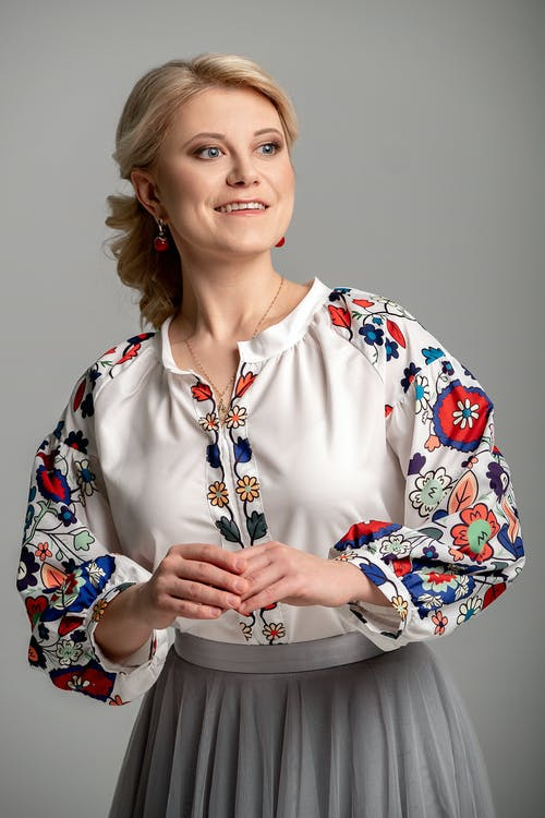 Woman in White Blue and Red Floral Button Up Shirt Smiling