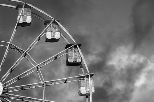 A Ferris Wheel and the Cloudy Sky in Black and White