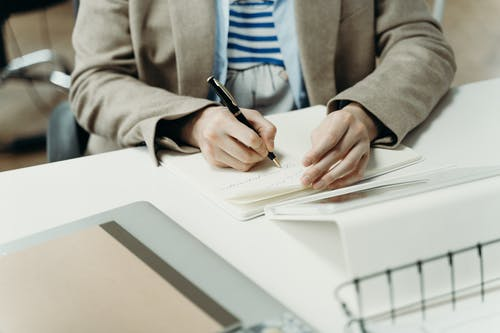 Person in Brown Blazer Writing on Notebook