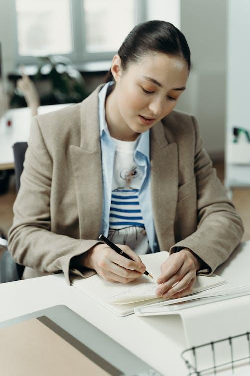 Woman in Brown Blazer Writing