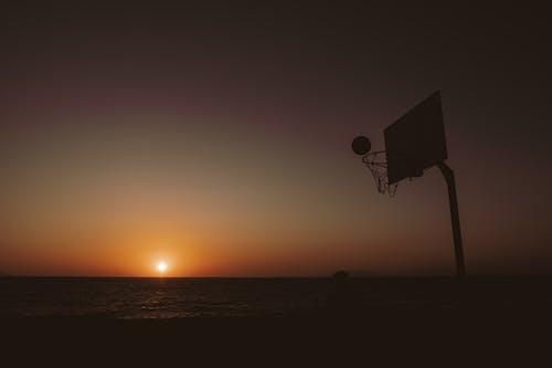 Basketball ring against sun on orange sky over serene sea at spectacular sunset
