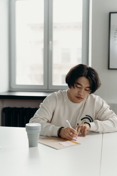 Man in White Sweater Writing on a Notepad