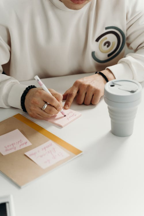 Person in White Long Sleeve Shirt Writing on a Sticky Note