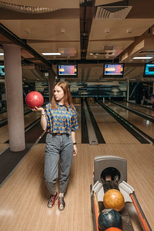 A Woman Gripping a Bowling Ball