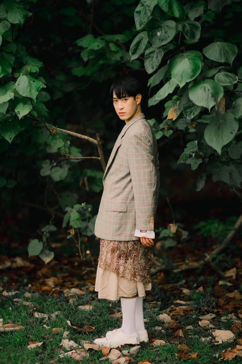 Woman in Gray Long Sleeve Shirt and Brown Skirt Standing Beside Green Leaves