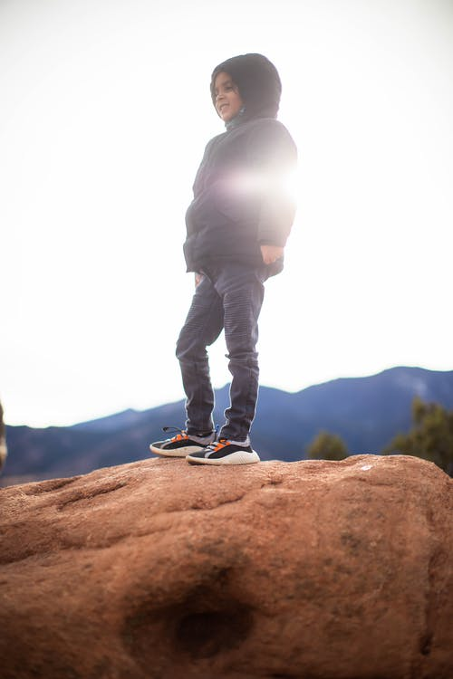 A Child in a Hoodie Jacket Standing on a Rock