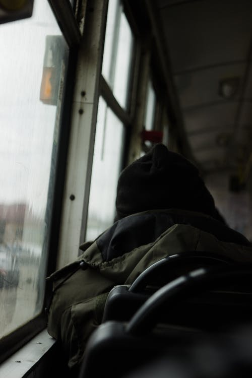Back view of unrecognizable male passenger in warm wear sitting on seat near window while riding public transport on street