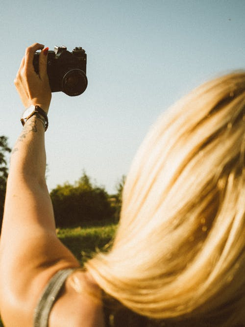 Back view of crop anonymous female traveler with long blond hair taking selfie on modern photo camera while standing in grassy field against cloudless blue sky on sunny day