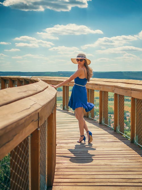 Woman in Blue Tank Top and Blue Shorts Standing on Brown Wooden Dock