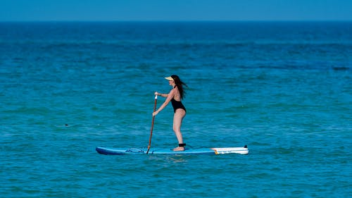 Side view of distant sporty female wearing swimsuit on stand up puddleboard surfing in endless rippling sea on summer day