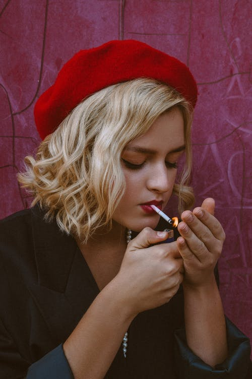 Young female in red beret and jacket lighting cigarette with lighter near weathered building wall in daytime