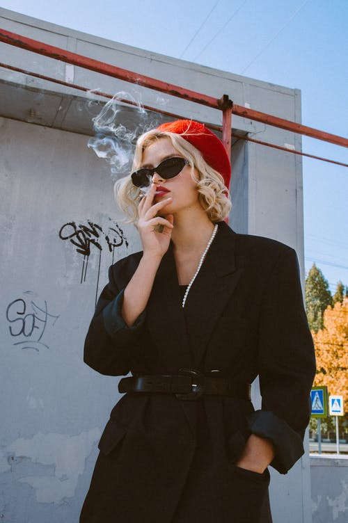 Lady with cigarette near building in street