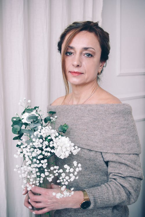 Woman in Gray Sweater Holding White Flowers