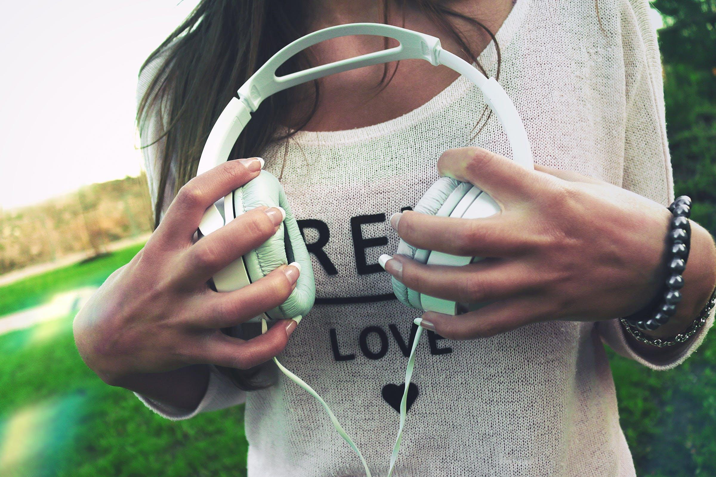 Woman Holding White Corded Headphones
