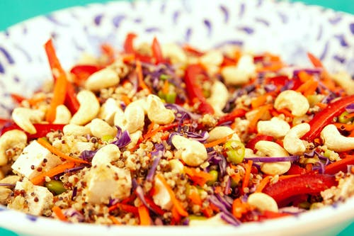 Closeup bowl of vegetarian salad made of couscous and pepper with cashew and tofu