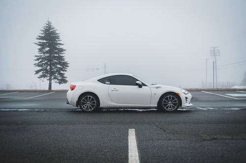 Modern white sport car parked against road marked parking area in empty foggy street near large pine tree