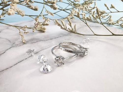 Pair of expensive engagement rings and shiny diamonds placed on marble table near natural plant twigs