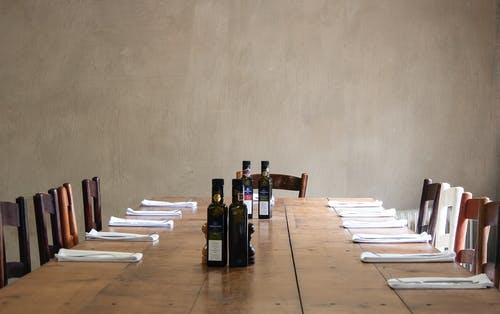Wooden table with bottles of olive oil and cutlery