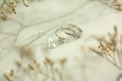 Silver rings and diamonds on marble surface