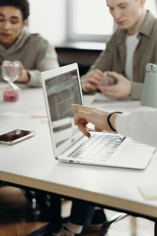 Person in White Long Sleeve Shirt Pointing on Laptop Screen