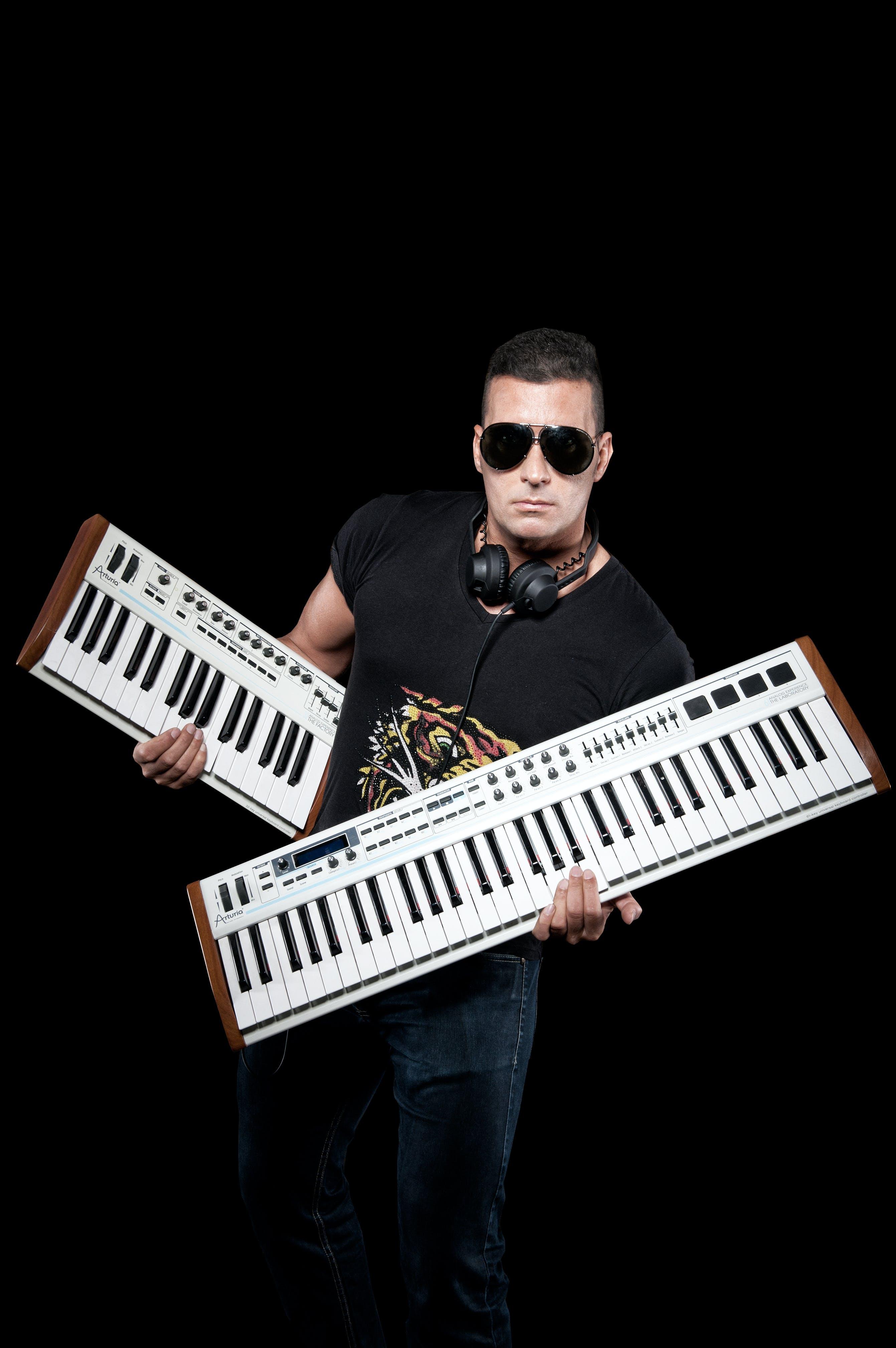 Man Wearing Black Crew-neck Shirt Holding White Keyboards