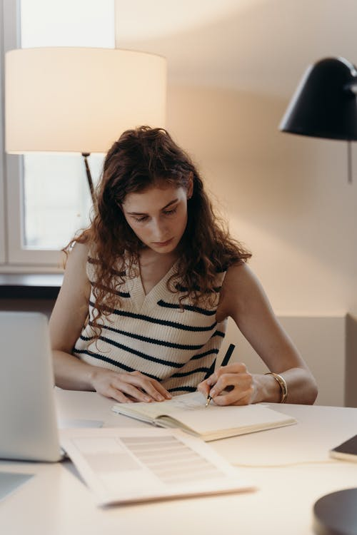 Woman in White and Black Stripe Top Writing