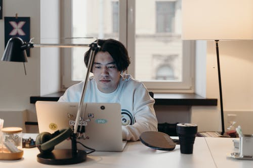 Man in White Sweater Using a Laptop