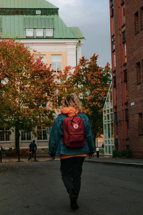 Back View of a Woman Walking with a Red Backpack
