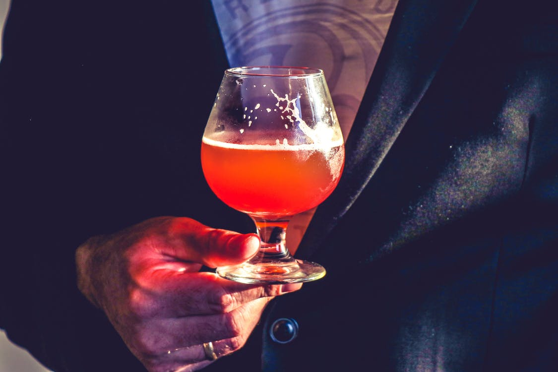 Person Holds Clear Glass Snifter With Red Beverage