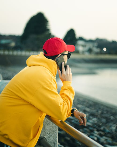 Woman in Yellow Hoodie and Red Knit Cap Sitting on Brown Wooden Bench
