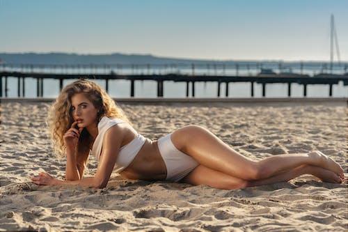 Beautiful Woman in a White Bikini Lying on the Sand