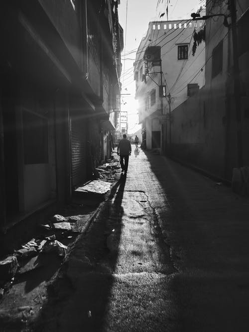 Grayscale Photo of a Person Walking in an Alley