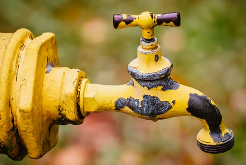 Close-Up Shot of a Yellow Steel Faucet