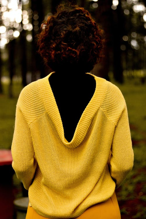 Woman in Yellow Knit Sweater Standing on Green Grass Field
