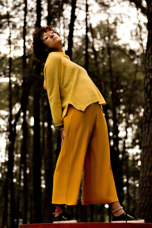 Woman in Yellow Long Sleeve Shirt and Brown Pants Standing in Forest