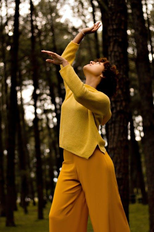 Woman in Yellow Sweater Raising Her Hands