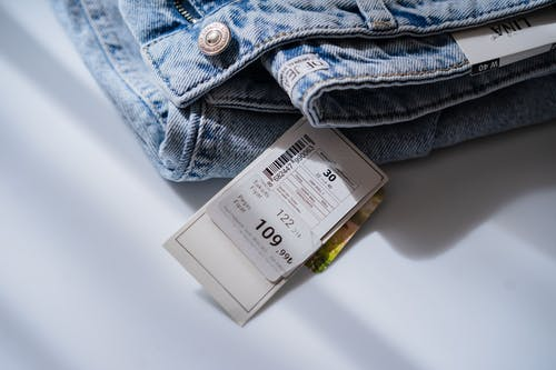 Jeans with price ticket on white table
