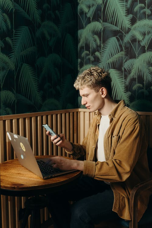 Man Using a Mobile Phone and Laptop
