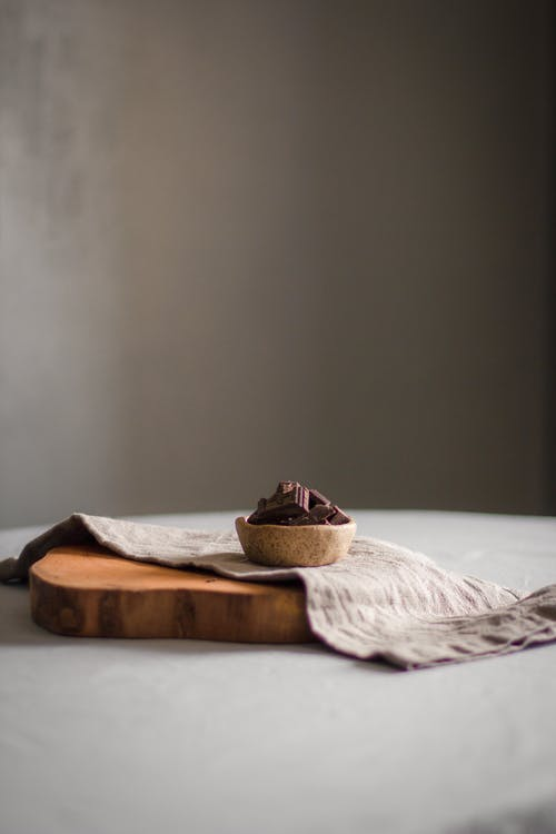 Sweet dark chocolate tart served on wooden board on round table in light room