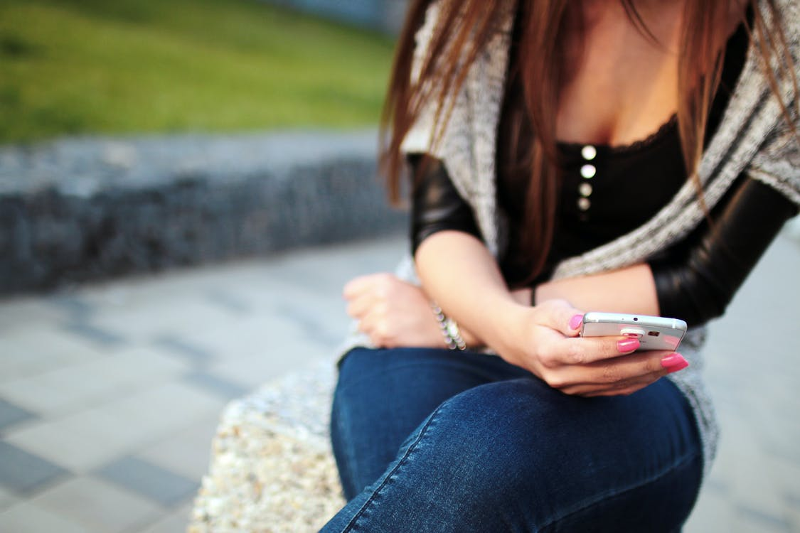 Woman in Black Elbow Sleeve Shirt and Blue Denim Jeans Sitting on the Grey Rock during Daytime