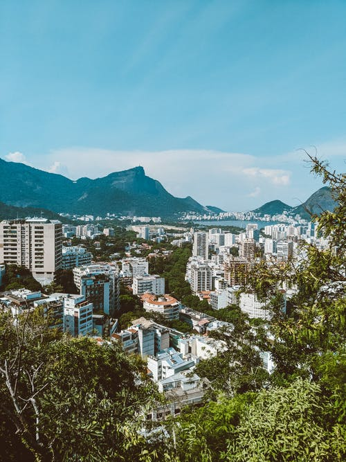 From above picturesque cityscape of Rio de Janeiro with residential buildings surrounded by green trees located on Atlantic ocean coast with hills and rocky mountains in sunny day