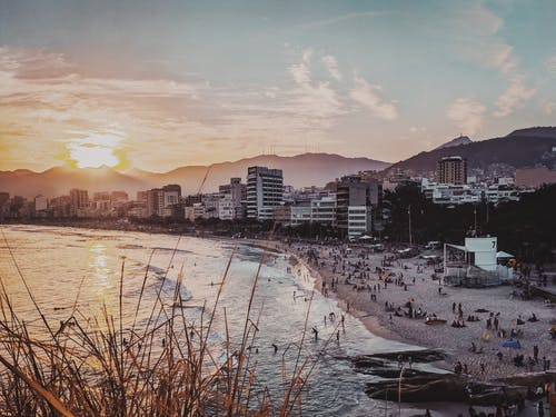 Rio de Janeiro coastline with modern buildings and people resting on sandy beach near calm ocean in evening time with sun setting over mountains