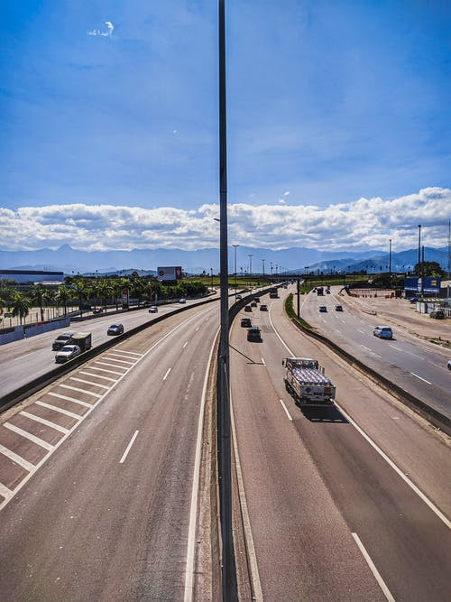 Curvy asphalt roadway with marking lines and vehicles leading to hills under blue sky with white clouds in sunny day