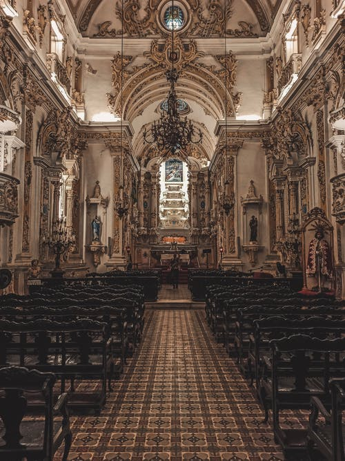 Aged baroque church interior with tiled floor and rows of pews between decorations on stone walls