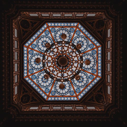 Chandelier on ornamental ceiling in old building