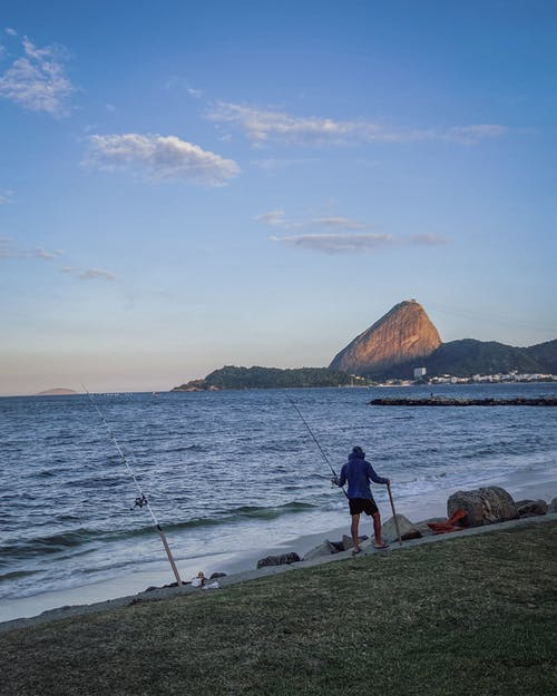 Unrecognizable fisherman catching fish in sea against mountain