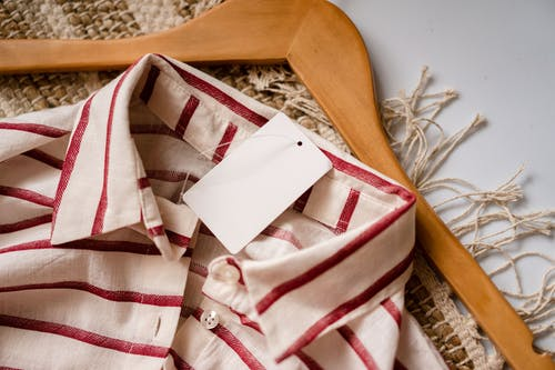 From above of casual shirt with red stripes and blank paper label placed on wooden hanger on rug